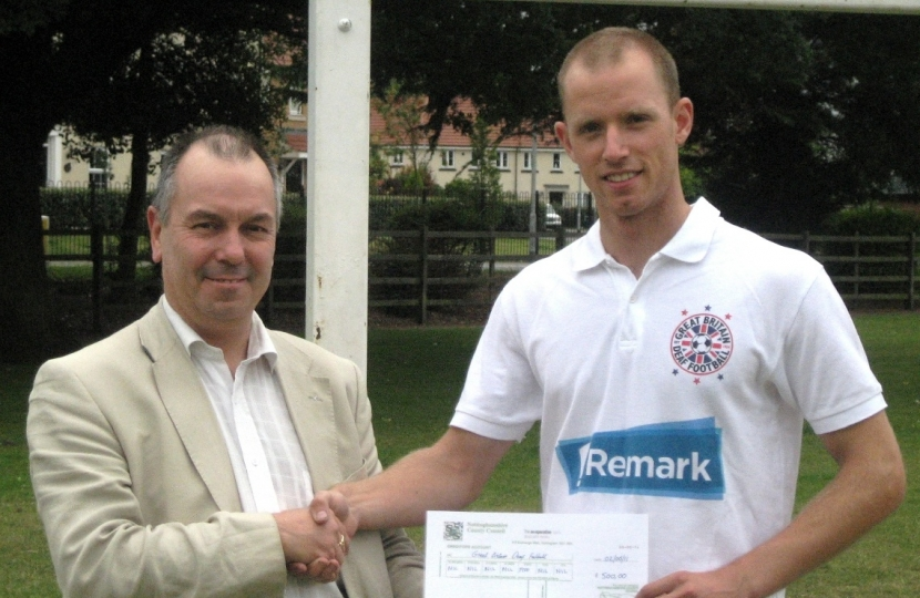 Cllr Eric Kerry presenting Jeremy Millensted with his CDF sponsorship cheque